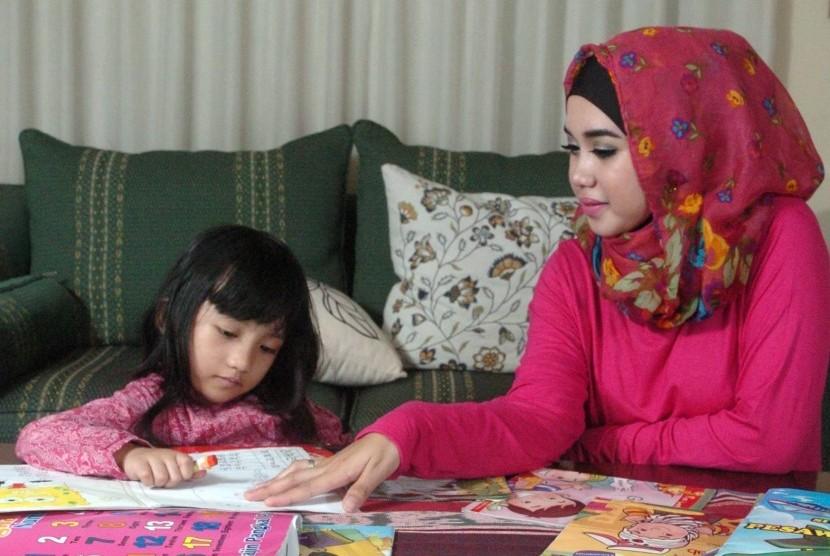 Anak dan ibu sedang belajar di rumah.