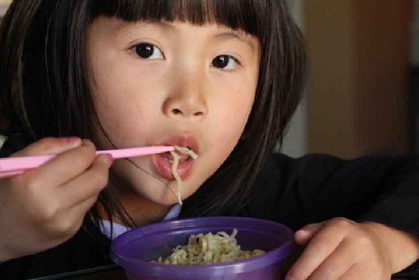 Anak makan mie instan (Ilustrasi)
