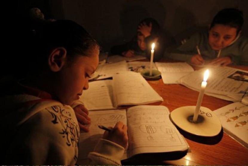 Anak sekolah Palestina mengerjakan pekerjaan rumah dengan penerangan lilin jelang dimatikannya listrik di Gaza City, Maret 2012