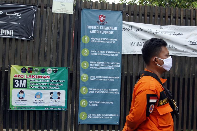 Anggota Badan Penanggulangan Bencana Daerah (BPBD) Kota Bogor berdiri di dekat pintu gerbang masuk Pondok Pesantren (Ponpes) Bina Madani di Kelurahan Harjasari, Kota Bogor, Jawa Barat, Selasa (8/6/2021). Sebanyak 65 santri dan pengurus di Ponpes itu terkonfirmasi positif COVID-19 setelah menjalani tes swab PCR yang saat hendak memulai pembelajaran tatap muka sehingga Ponpes tersebut ditutup untuk sementara waktu.