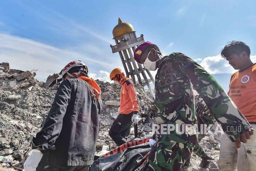 Anggota Basarnas bersama TNI dan relawan membawa kantong berisi jenazah korban gempa dan tsunami di Balaroa, Palu, Sulawesi Tengah, Kamis (4/10).