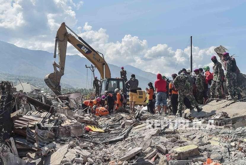 Anggota Basarnas bersama TNI dan relawan menggunakan alat berat melakukan pencarian jenazah korban gempa dan tsunami di Balaroa, Palu, Sulawesi Tengah, Kamis (4/10).
