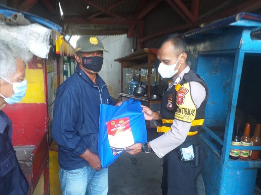 Anggota Bhabinkamtibmas Polres Sukabumi membagikan bantuan beras kepada warga terdampak PPKM, Rabu (21/7) lalu