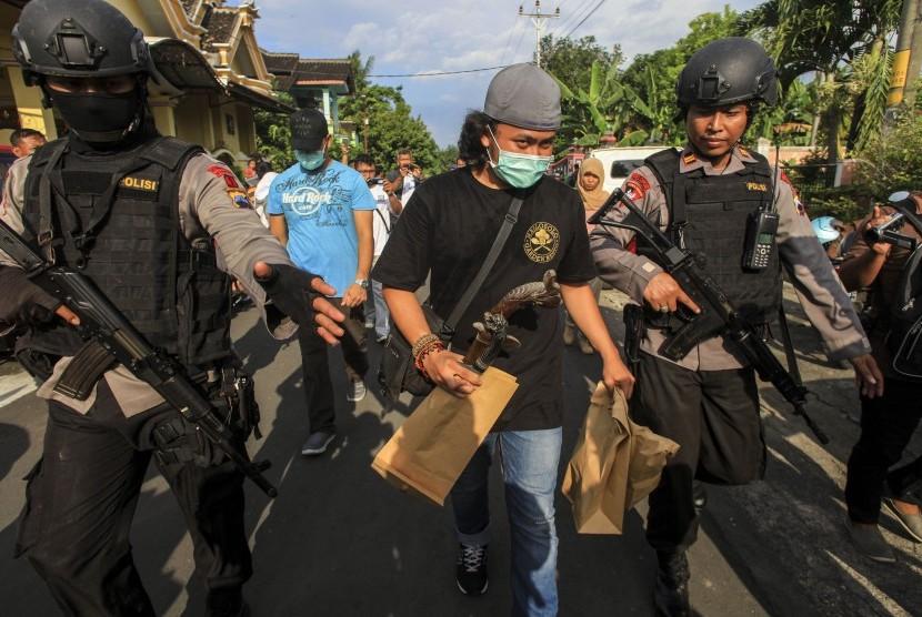 Anggota Datasemen Khusus (Densus) 88 antiteror Mabes Polri membawa barang bukti milik terduga teroris jaringan Nur Rohman, Haryanto alias Hasan di Makam Haji, Sukoharjo, Jawa Tengah, Selasa (19/7).
