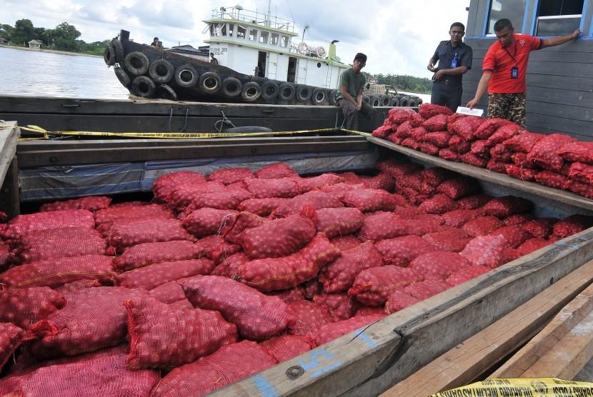 Anggota Ditpolair Polda Jambi memeriksa barang bukti tangkapan bawang merah selundupan saat akan diamankan ke Markas Unit Patroli Angsoduo Ditpolair Polda Jambi di tepian Sungai Batanghari, Kasang, Jambi, Senin (25/4).