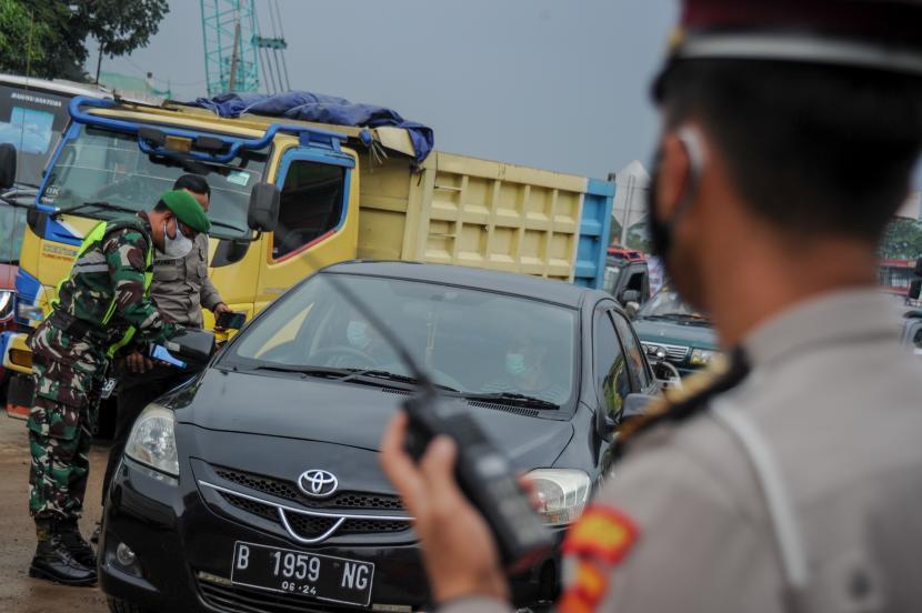 Anggota Kepolisian dan TNI memeriksa surat keterangan sehat dari pengendara luar Bandung saat operasi PPKM Mikro di Gerbang Keluar Tol Cileunyi, Kabupaten Bandung, Jawa Barat, Jumat (18/6/2021). Penyekatan kendaraan dari luar Bandung tersebut dilakukan setelah Jawa Barat dinyatakan siaga satu COVID-19 serta ditujukan untuk mencegah penyebaran COVID-19 di wilayah Bandung Raya.