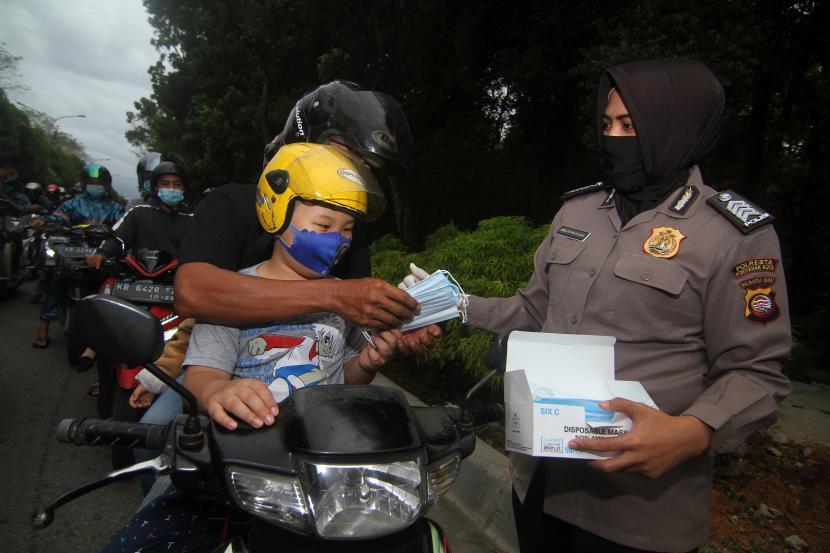 Anggota kepolisian membagikan masker (ilustrasi).