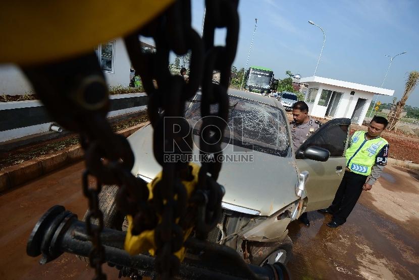 Anggota kepolisian memeriksa mobil yang telah mengalami kecelakaan ruas Jalan Tol Cipali, Subang, Jawa Barat.