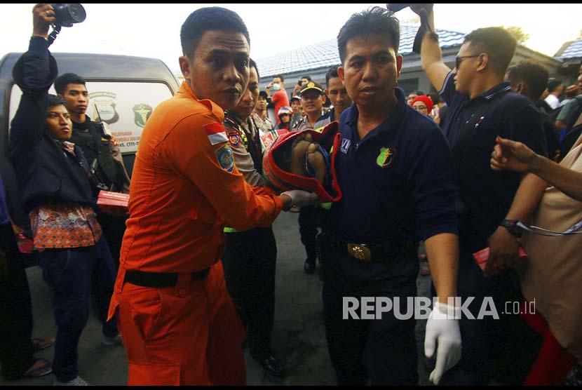 Anggota kepolisian mengangkat jenazah salah satu korban kapal motor Arista yang tenggelam di Rumah Sakit Jala Ammari, Makassar, Sulawesi Selatan, Rabu (13/6).