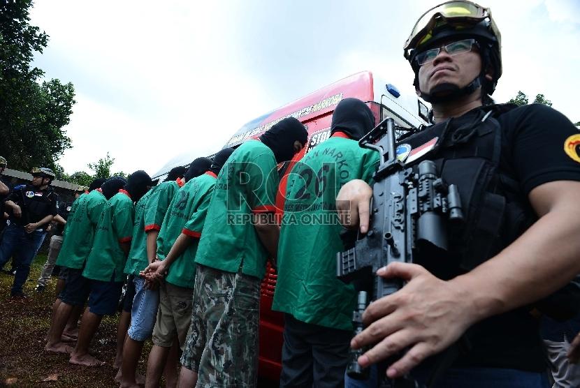 Anggota kepolisian menjaga tersangka pemilik barang bukti narkoba saat pemusnahan barang bukti narkoba di lapangan Polsek Palmerah, Jakarta Barat, Rabu (11/3). (Republika/Raisan Al Farisi)