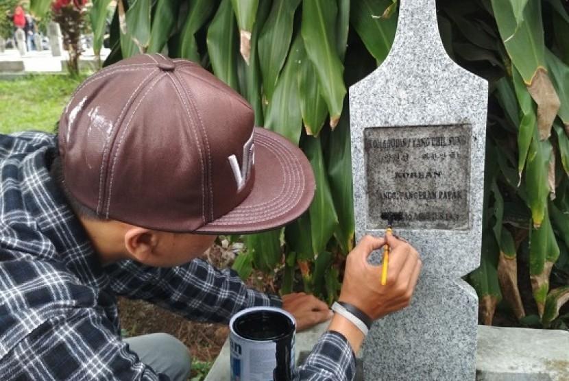 Anggota Komunitas Nusa Karya membersihkan makam Yang Chill Seoung asal Korea Selatan di Tenjolaya, Kecamatan Terogong Kidul, Garut, Kamis (9/11). Dia memilih berganti nama menjadi Komaruddin dan dimakamkan bersama pahlawan Indonesia lainnya