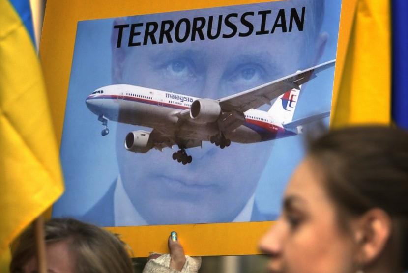 Anggota komunitas Ukraina membawa poster menolak Presiden Rusia, Vladimir Putin menghadiri pertemuan pimpinan G20 November mendatang. Mereka menyalahka Putin atas jatuhnya pesawat Malaysia Airlines MH17