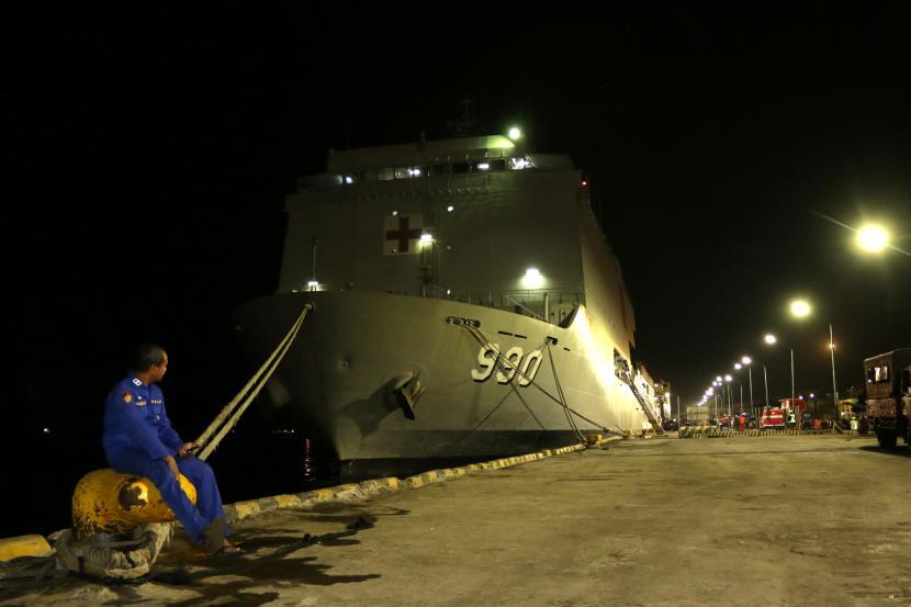 Anggota polisi duduk di depan KRI Dr Soeharso-990 yang sandar di Pelabuhan Tanjung Wangi, Banyuwangi, Jawa Timur, Jumat (23/4/2021). Hari ke-3 pencarian Kapal Selam KRI Nanggala-402 yang hilang kontak saat menggelar latihan penembakan di utara Bali, KRI Dr Soeharso 990 kembali ke pelabuhan Tanjung Wangi untuk mengisi BBM dan logistik.