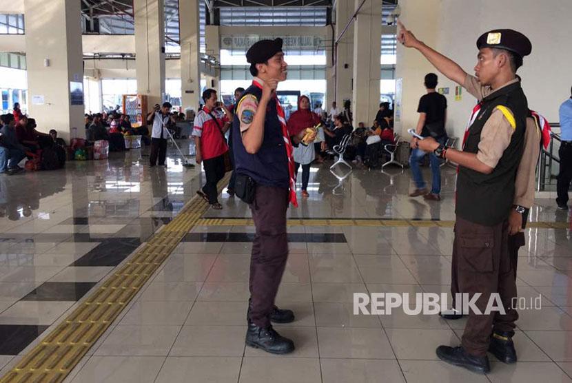 Anggota Pramuka dikerahkan di Terminal Pulogebang, memberikan arahan kepada penumpang yang menanyakan bus tujuannya.