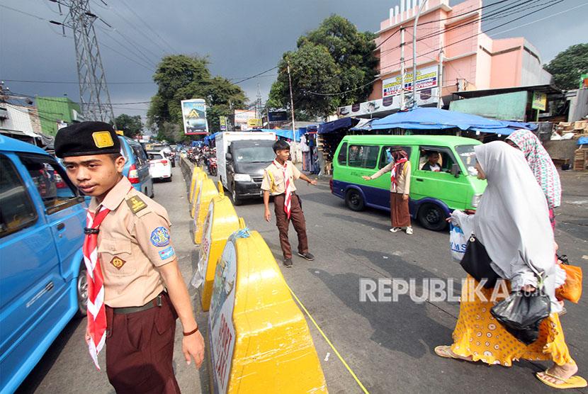 Anggota Pramuka mengatur lalu lintas di jalur mudik Ciawi-Sukabumi , Bogor, Jawa Barat, Selasa (12/6).