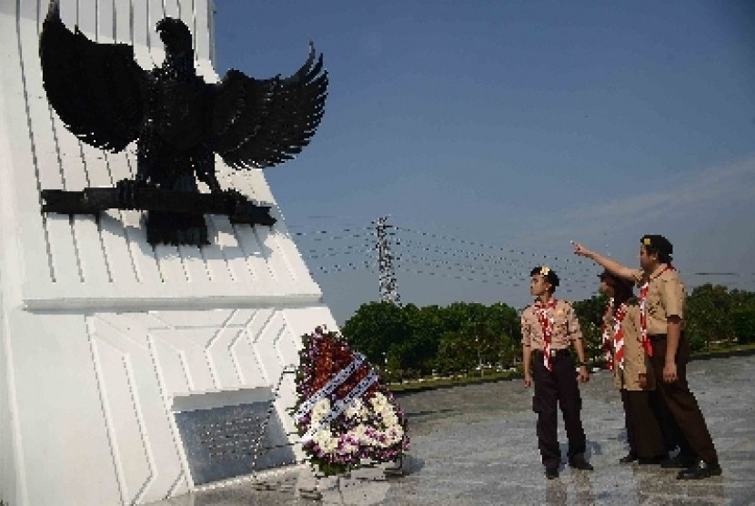 Anggota Pramuka Penegak melihat Burung Garuda saat berziarah ke makam pahlawan Kalibata, Jakarta Selata