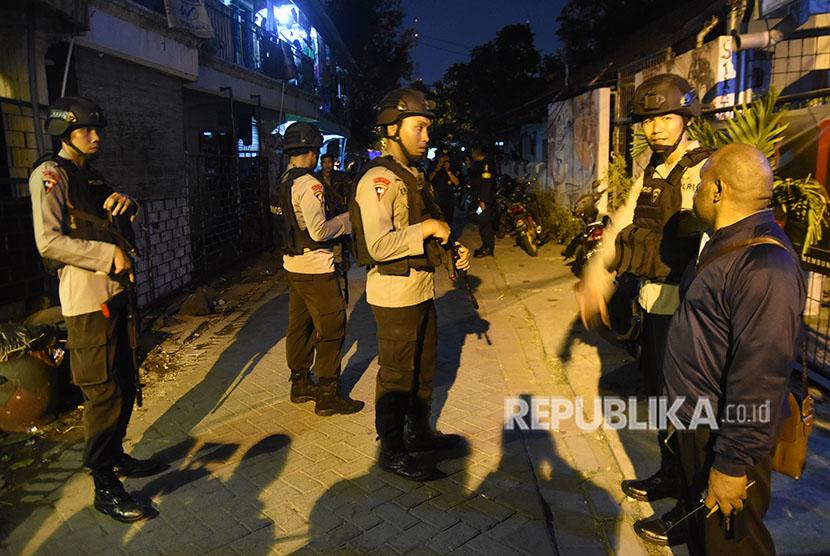 Anggota Satbrimob Polda Jawa Timur berjaga di lokasi penggeledahan rumah terduga teroris di kawasan Sikatan, Manukan Wetan, Surabaya, Jawa Timur, Selasa (15/5).