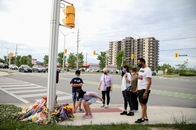 Serangan Islamofobia, Satu Keluarga Muslim di Kanada Tewas. Anggota Selamati meletakkan bunga tanda berduka di lokasi penabrakan keluarga Muslim di London, Ontario, Kanada, 7 Juni 2021. Polisi mengatakan serangan tersebut merupakan kejahatan kebencian anti-Islam.