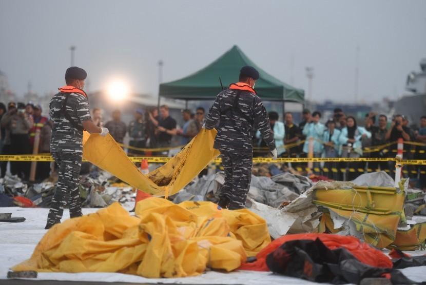 Anggota TNI AL membawa kantung jenazah korban jatuhnya pesawat Lion Air bernomor registrasi PK-LQP dengan nomor penerbangan JT 610 di Pelabuhan Tanjung Priok, Jakarta, Kamis (1/11/2018).