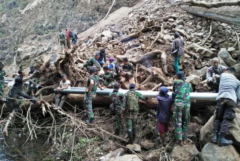 Anggota TNI dan Polri yang tergabung dalam Komando Tugas Gabungan Terpadu (Kogasgabpad) wilayah Sektor 2 menyambungkan pipa air bersih yang sempat terputus akibat gempa di Desa Senaru, Kecamatan Bayan, Lombok Utara, pada Rabu (5/9).