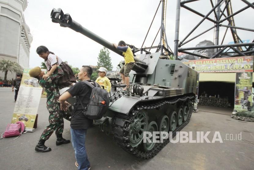 Anggota TNI membantu anak-anak menaiki tank (ilustrasi)