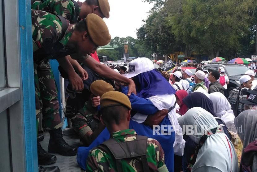 Anggota TNI membantu massa aksi Reuni 212 menyeberang jalan melewati halte Juanda, Ahad (2/12).