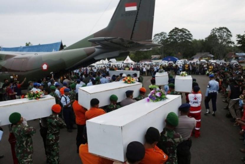Anggota TNI membawa peti jenazah ke dalam pesawat untuk diterbangkan ke Surabaya.