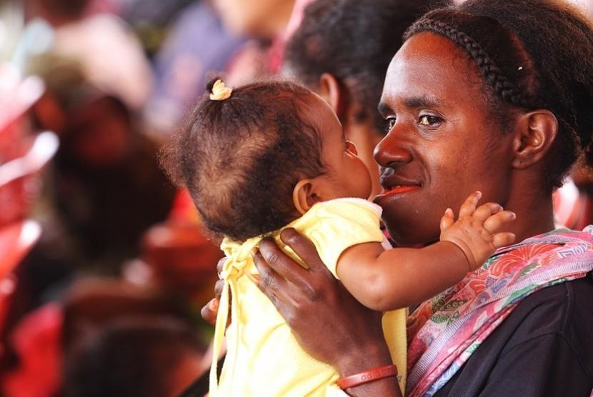 ANGKA KEMATIAN IBU DAN ANAK. Seorang ibu bercanda dengan anaknya sebelum melakukan pemeriksaan kesehatan bayi di Posyandu Kama di Wamena, Kabupaten Jayawijaya, Papua, Kamis (18/4).