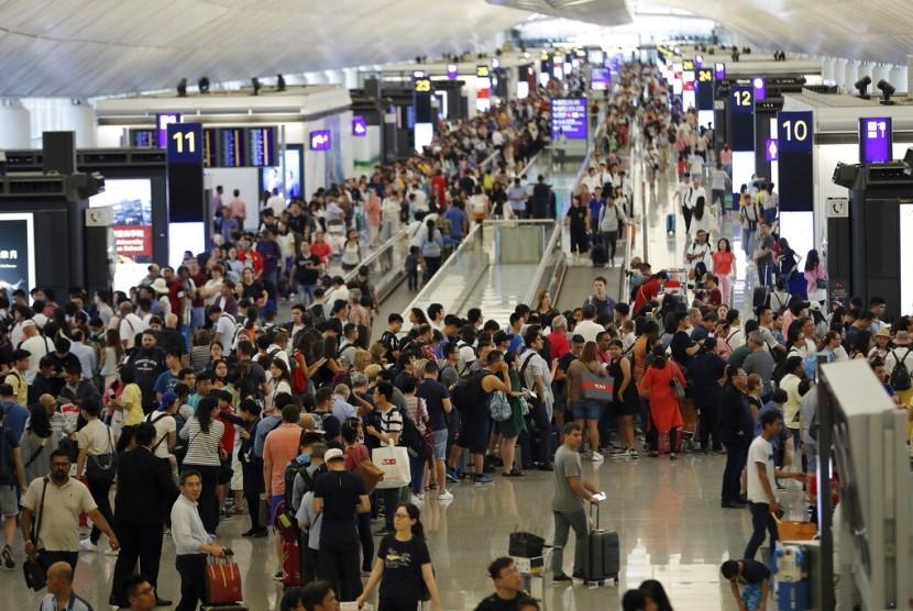 Antrean penumpang mengular di terminal kedatangan di Bandara Internasional Hong Kong di Hong Kong akibat aksi protes, Senin (12/8).
