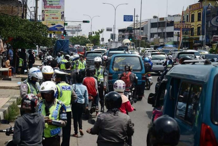 Aparat kepolisian memeriksa kelengkapan surat kendaraan pengendara motor saat menggelar operasi Zebra Jaya 2014 di Jalan Margonda Raya, Depok, Jumat (28/11).    (Republika/Raisan Al Farisi)