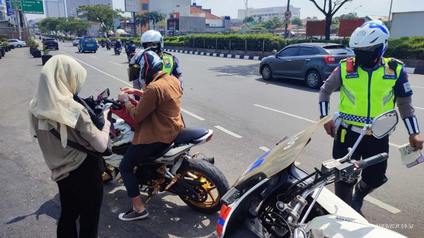 Aparat Satuan Lalu Lintas Polres Metro (Satlantas Polrestro) Depok menindak pengendara motor yang melanggar di Jalan Margonda Raya, Kota Depok.