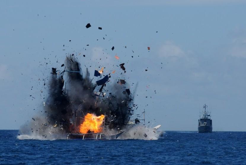 Api dan asap keluar dari lambung kapal nelayan asing pelaku ilegal fishing yang ditenggelamkan di perairan Bitung, Sulawesi Utara, Rabu (20/5).  (Antara/Fiqman Sunandar)