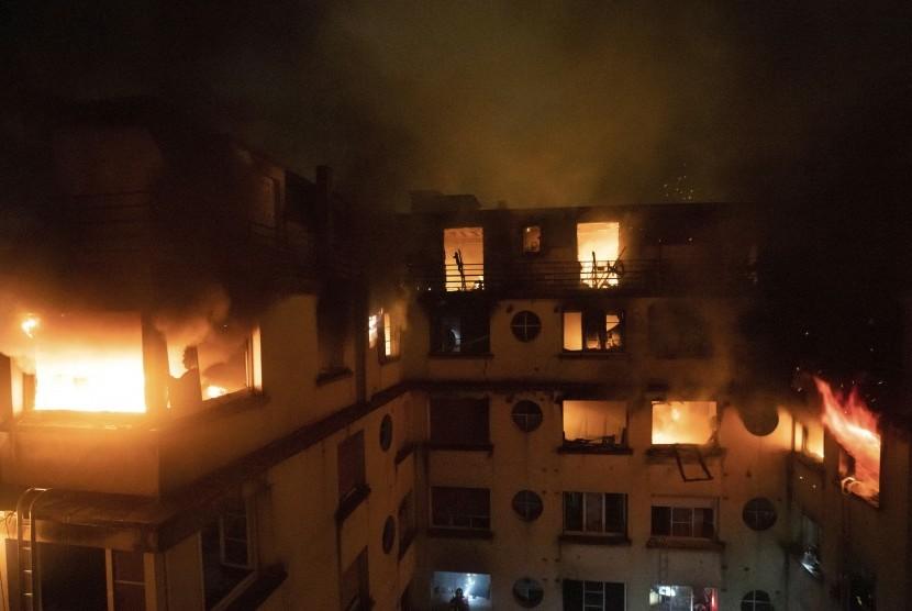 Api menjilat lantai atas gedung apartemen di Paris, Prancis, Selasa (5/2). Aparat keamanan telah mengamankan seorang perempuan yang diduga sengaja melakukan pembakaran.
