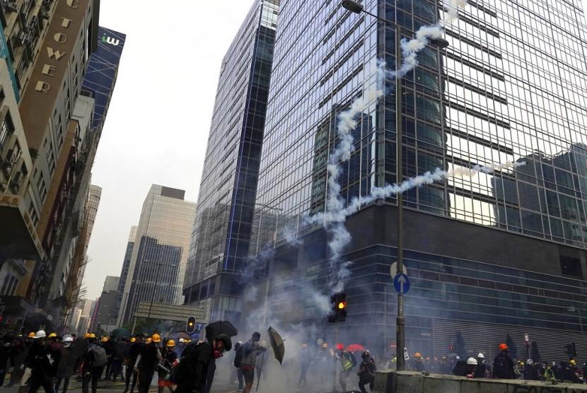 Asap keluar akibat tembakan gas air mata ketika petugas keamanan dan pengunjuk rasa ricuh di Hong Kong, Sabtu (24/8).