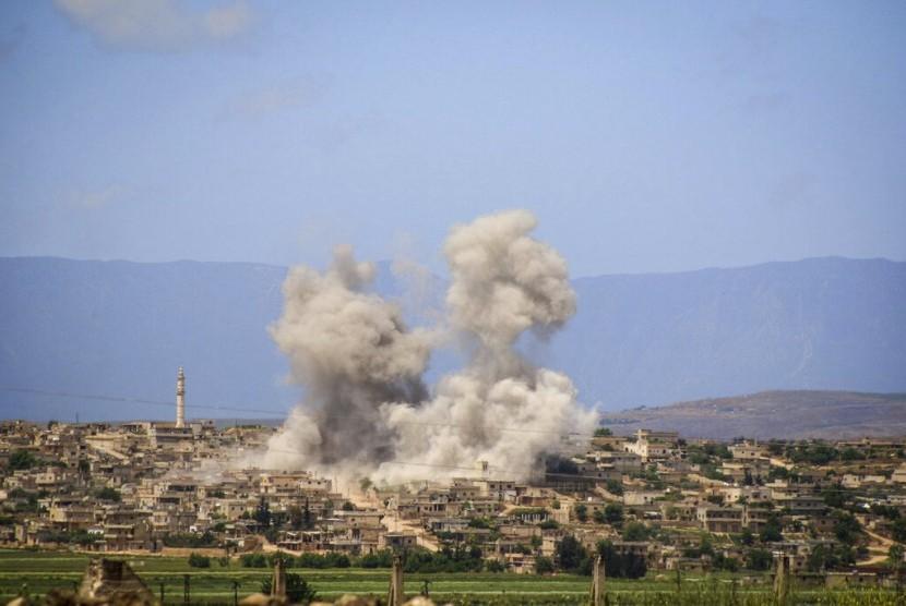 Asap membumbung setelah serangan udara pasukan Suriah dan Rusia mengenai kota al-Habeet, selatan Idlib, Suriah, Ahad (19/5).