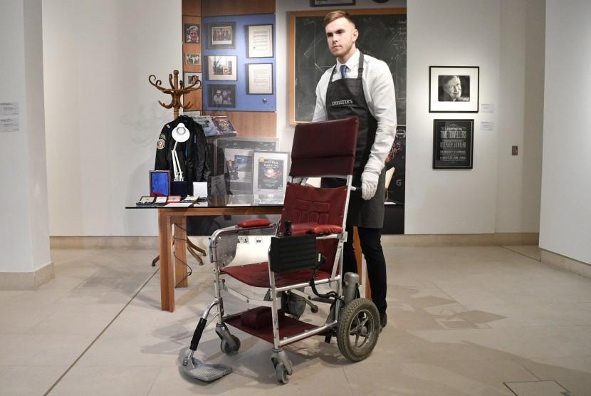 Asisten galeri memperlihatkan kursi roda bermotor milik Profesor Stephen Hawking dari tahun 1988 dalam lelang di Christies Auction House, London, Inggris, (30/10).