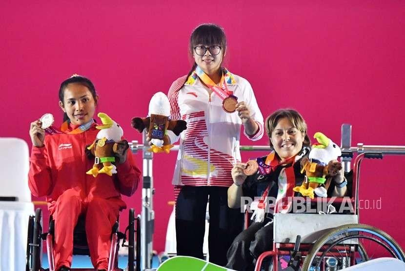 Atlet Cina Cui Zhe (tengah) bersama Atlet Indonesia Ni Nengah Widiasih (kiri) dan Atlet Suriah Noura Baddour (kanan) mengangkat medali Women's Up to 41 kg Group A para powerlifting Asian Para Games 2018 di Balai Sudirman, Jakarta, Ahad (7/10).