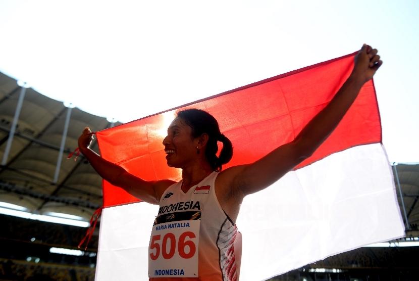 Atlet Indonesia Maria Natalia Londa membawa bendera merah putih usai mendapatkan perak pada nomor Lompat Jangkit SEA Games 2017 Kuala Lumpur di Stadion Bukit Jalil, Malaysia, Rabu (23/8).