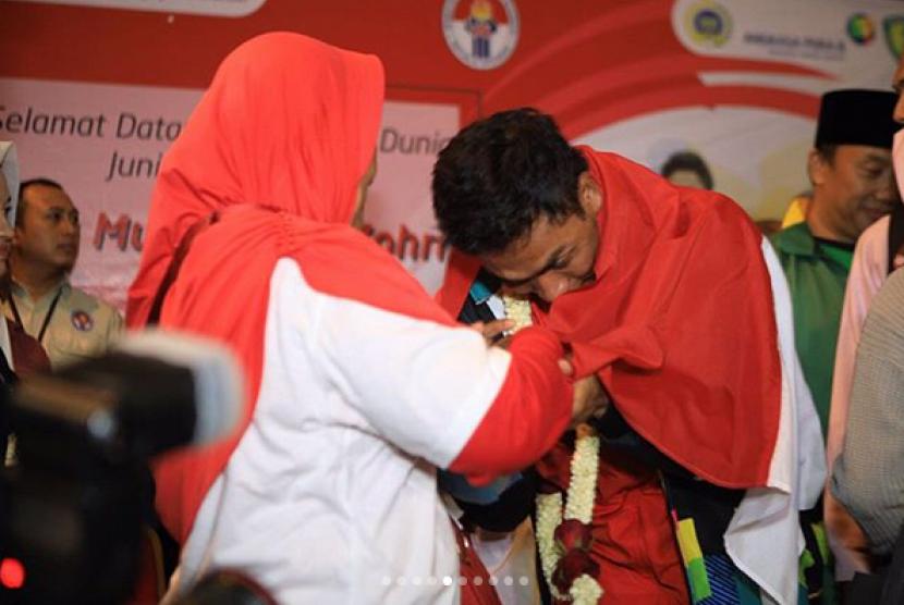 Atlet lari yang berhasil meraih juara dunia lari 100 meter, Lalu Muhammad Zohri menangis saat diselimuti bendera merah putih oleh kakaknya dalam penjemputan kedatangannya di Bandara Soekarno Hatta, Selasa (17/7) malam.