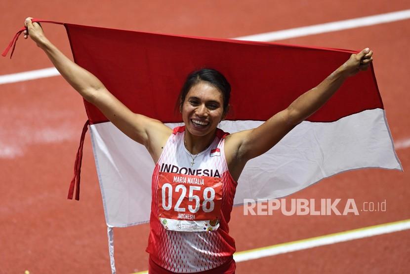 Atlet lompat jauh Indonesia Maria Natalia Londa membentangkan Bendera Merah Putih setelah berhasil memenangkan pertandingan Final Lompat Jauh Putri SEA Games ke-30 di Stadion Atletik New Clark, Filipina, Ahad (8/12/2019).