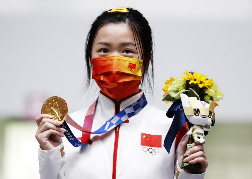 Atlet menembak asal China, Qian Yang, memamerkan medali emas yang diraihnya dari nomor air rifle 10 meter putri, Sabtu (24/7). Yang menjadi atlet pertama yang meraih emas pada Olimpiade Tokyo.