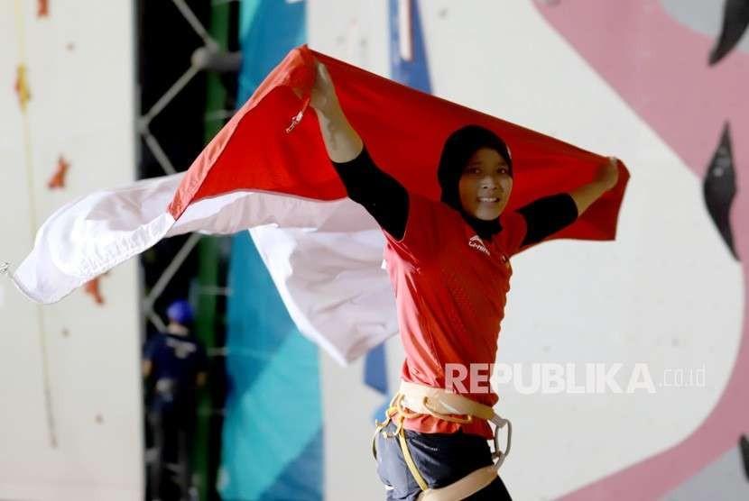 Atlet panjat tebing Indonesia Aries Susanti Rahayu mengibarkan Bendera Merah Putih setelah berhasil meraih medali emas pada kategori speed Asian Games 2018 di Arena Panjat Tebing Jakabaring Sport City, Palembang, Sumatera Selatan, Kamis (23/8).
