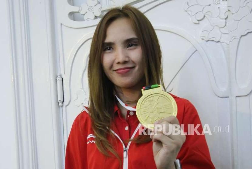 Atlet pencak silat putri peraih medali emas Wewey Wita memperlihatkan medalinya di sela-sela acara Pemberian Penghargaan Kepada Atlet Asian Games 2018 Asal Jawa Barat, di Gedung Pakuan, Kota Bandung, Selasa (4/9).