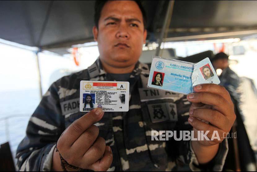 Awak KRI Kobra 867 Letnan Satu Fadhillah menunjukkan kartu identitas dari tas yang ditemukan di lokasi jatuhnya pesawat Lion Air JT 610 di perairan Laut Jawa, Senin (29/10)