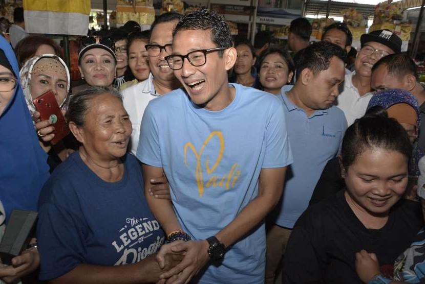 Bakal Calon Wakil Presiden Sandiaga Uno (tengah) berbincang dengan pedagang saat mengunjungi Pasar Sindhu di Sanur, Denpasar, Bali, Ahad (9/9).