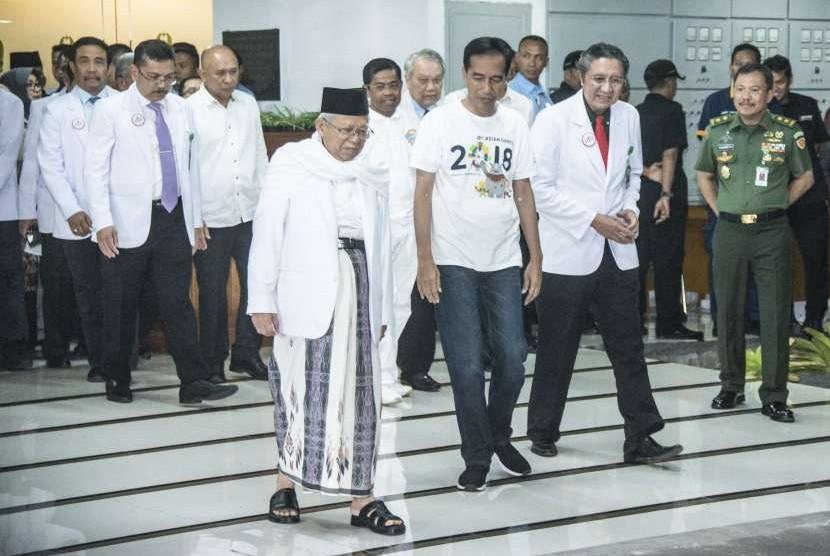 Bakal capres-cawapres Pilpres 2019, Joko Widodo (ketiga kanan) dan Ma'ruf Amin (keempat kiri), berjalan keluar seusai menjalani tes kesehatan di RSPAD, Jakarta, Ahad (12/8).