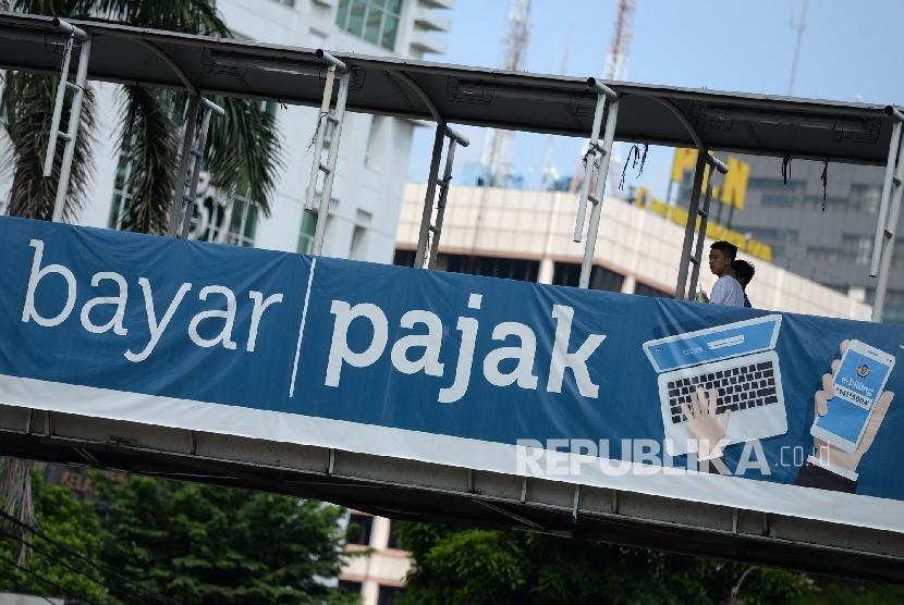 Baliho himbauan membayar pajak dipajang di JPO Gambir, Jakarta, Ahad (24/4).(Republika/ Wihdan)