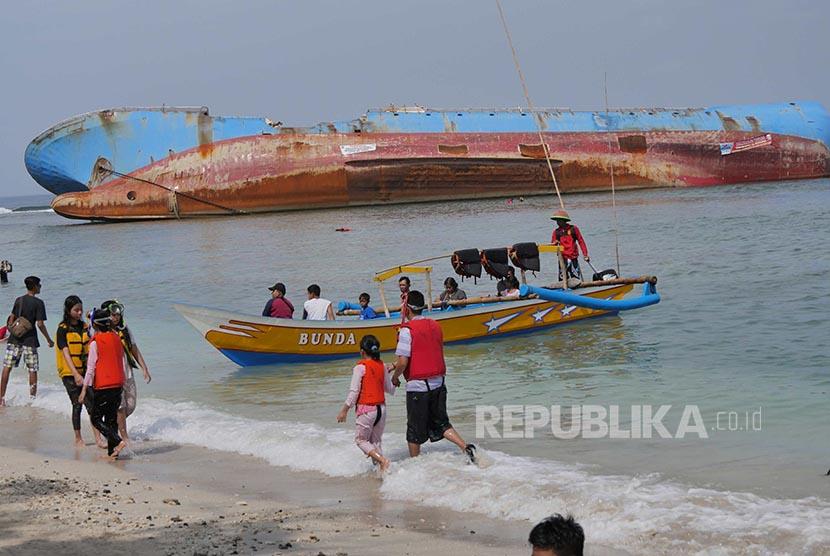 Wisatawan menikmati suasana Pantai Pasir Putih dengan latar Bangkai Kapal FV Viking di pesisir Pantai Timur Pangandaran