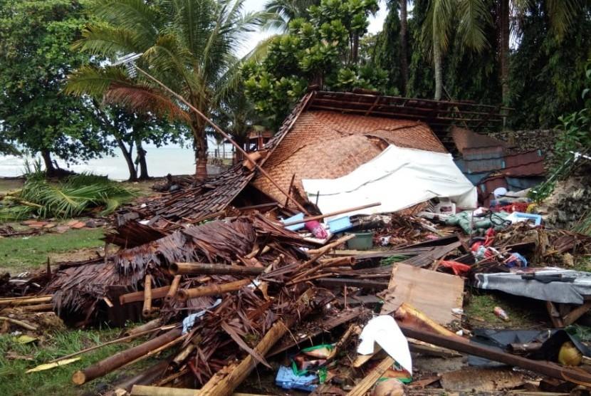 Bangunan porak-poranda dan kendaraan rusak akibat diterjang tsunami di Jalan Raya Anyer, Banten, Ahad (23/12).