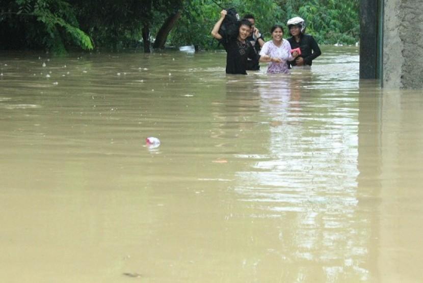 Warga membawa barang mereka melintasi banjir yang menggenangi Perumahan Bintang Alam, Telukjambe Timur, Karawang, Jabar.